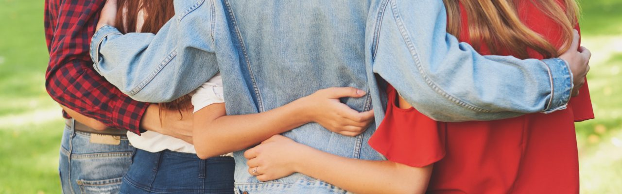 Stock image of young people from behind, displaying their arms linked around each others' shoulders and waists