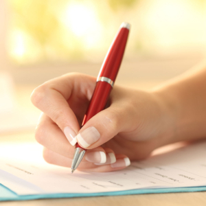 Stock photo in extreme close up of a hand filling out paperwork with a red pen