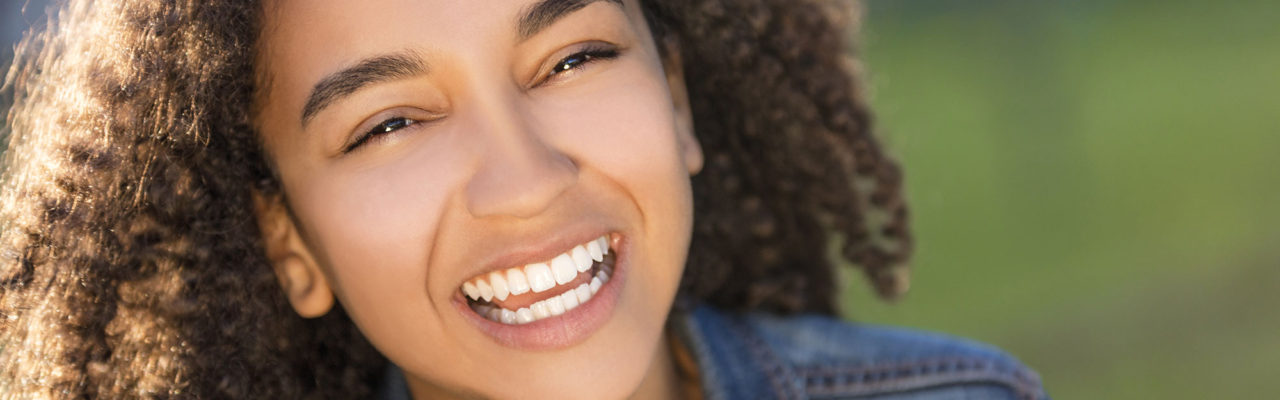 Stock image of a young girl smiling outside